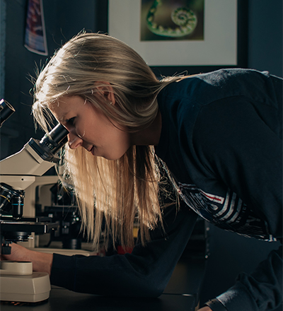A female student looking into a microscope
