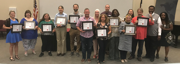 CCA instructors and faculty hold up plaques for completing their ACUE certification.