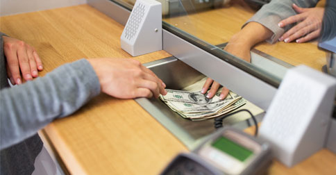 A person passing money through a teller's banking window