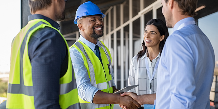 A man in a construction helmet shakes the hand of another man while a woman looks on.