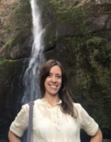 Jackie Zvejnieks standing in front of a waterfall
