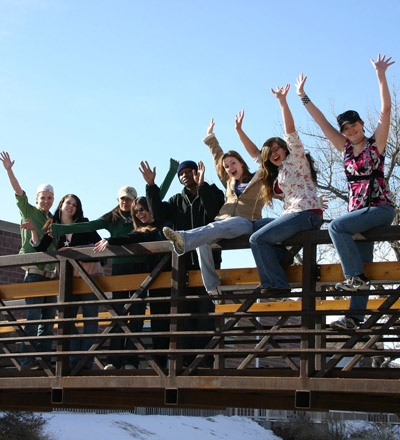 Students on a bridge raising their hands in the air