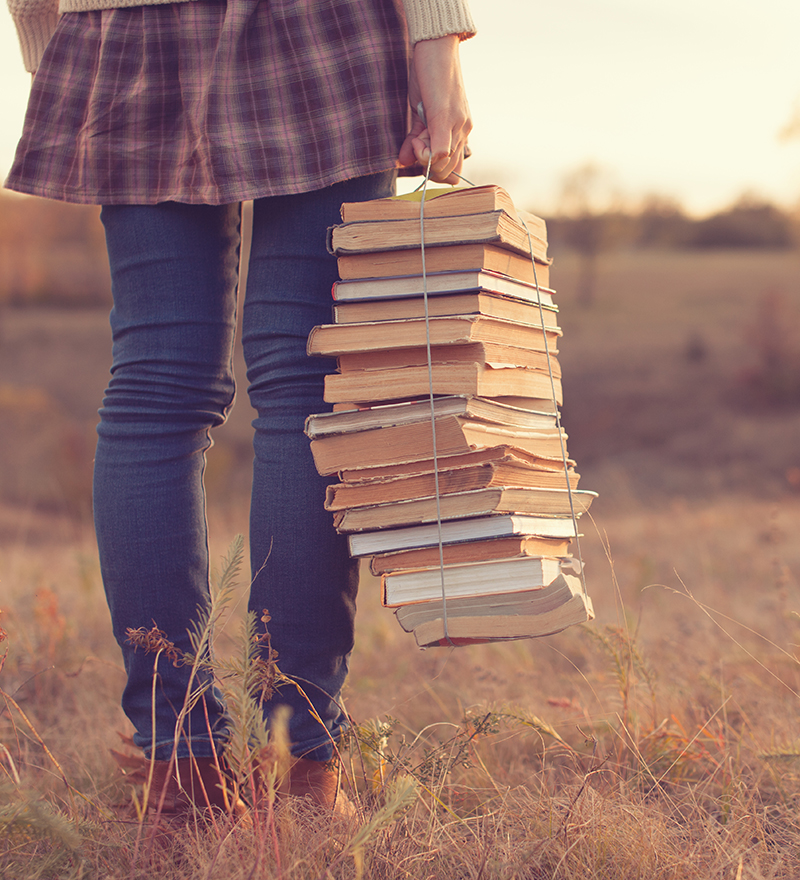 Girl holding stack of books in one hand, tied by shoestring