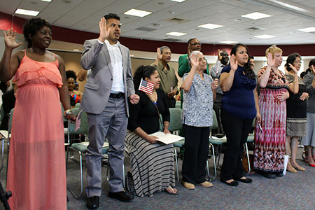 New U.S. citizens swear at a citizenship ceremony at CCA
