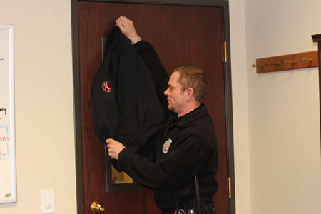Jeff Simpson demonstrates how to cover a door with a coat during a lockdown drill