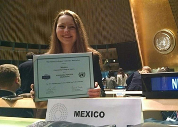 Isabel Rayborn holds up the Honorable Mention award CCA's Model United Nations team won inside the UN General Assembly Hall