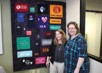 Debbie Irvine poses with a quilt that was sewn by Kimberly Suazo, payroll accountant.