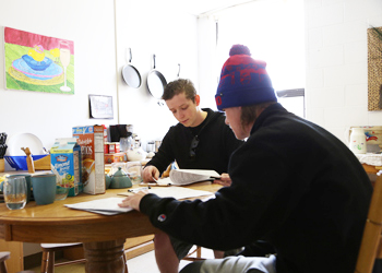 Students Nick Musial (left) and Michael Bartels (right) examine case files and try to determine who committed a crime during the Murder Most Foul exercise on March 14.