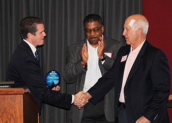 CCAF Executive Director John Wolfkill shakes Jim Lewien hand and presents him with an award