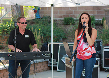 CCA faculty Michael Pickering plays the keyboard while his wife, Amy, sings during Music in the Park
