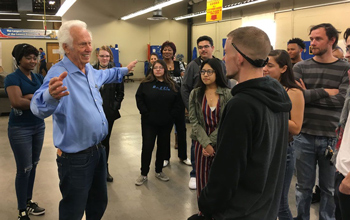 American Furniture Warehouse CEO Jake Jabs speaks to CCA students during a tour