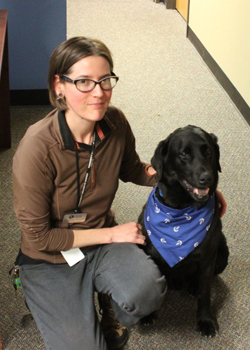 Adrienne Kruger, academic program support specialist, poses with Art faculty Kate O'Donnell's dog, Ness.