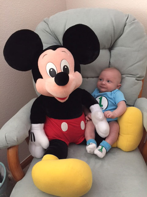 Micah Shulman sitting next to a stuffed Mickey Mouse