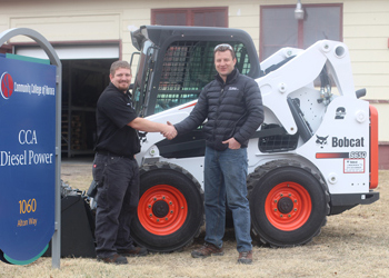 At left, Andrew Singer, of the Diesel Power Mechanics program, shakes the hand of Jason Kelley, governmental and national account specialist for Bobcat of the Rockies.