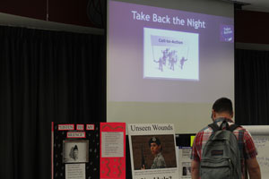 A student strolls by some of the student presentations at the CCA Take Back the Night event