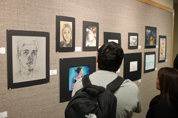 Students look at images on the walls of the Classroom Building during the Art Showcase on April 28.