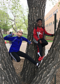 Faith Samuel and Joseph Lawrence hang out in a tree during Take Your Child to Work Day at CCA. They are the children of Michelle Samuel and Daniel lawrence