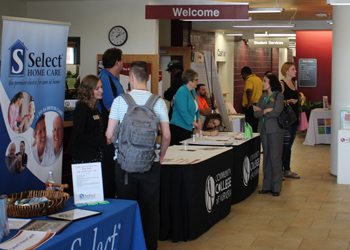 Students and others view tables and meet with the employers during the spring career expo