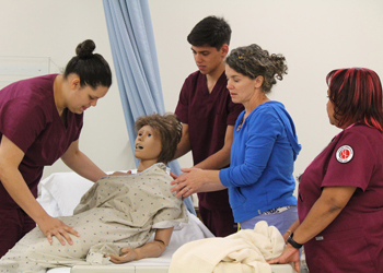 Students move a dummy from a bed to a wheelchair during a CNA class