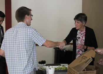 President Betsy Oudenhoven greets Todd Santee during Pizza with the President