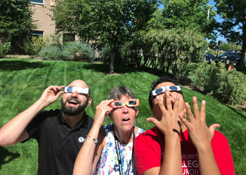 Jorge Velasquez, assistant director of Student Life, CCA President Betsy Oudenhoven, and Noel Chavez-Guizar, college recruiter for Recruitment and Orientation, take in the eclipse on Aug. 21 during the first day of classes.