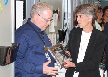 Greg Moore receives a plaque from CCA President Betsy Oudenhoven for his time at CCA