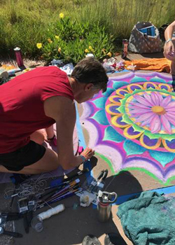 CCA President Betsy Oudenhoven adds to the chalk drawing during the Aurora Municipal Garden event