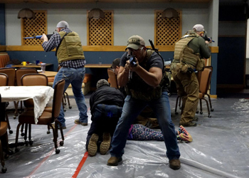 A person is worked on while armed guards stand watch during a simulation at the Disaster Management Institute.