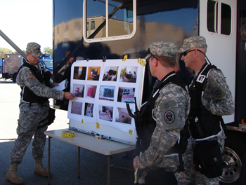 Military personnel go over a simulation strategy during a simulation at the Disaster Management Institute.