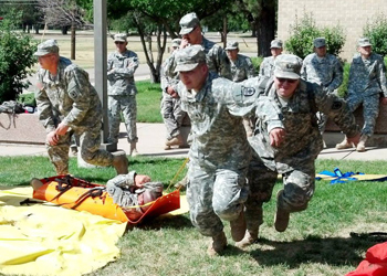 Military personnel drag a person away from the Disaster Management Institute during a simulation.