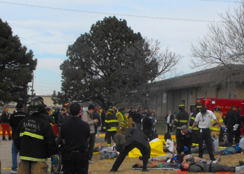 Emergency personnel and firefighters tend to victims during a simulation outside of the Disaster Management Institute.