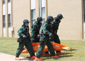 Emergency personnel carry a device toward the Disaster Management Institute during a simulated exercise.