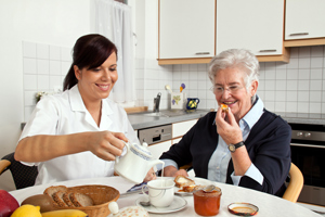 A nurse assisting an elderly woman during breakfast