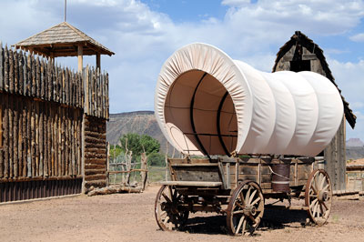 A covered wagon near an old west outpost