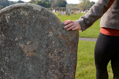 A person holding their hand atop a gravestone