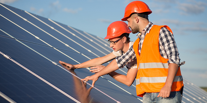 Two men in construction gear look at solar panels on a building.