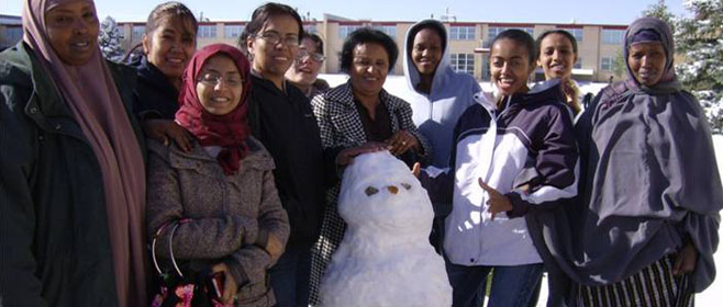A group of ESL students gather around a snowman in front of a Lowry building in Denver Colorado