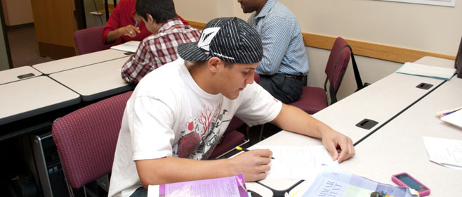 An ESL student works on a paper in a Lowry classroom in Denver Colorado