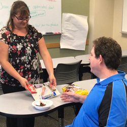 Career Counselor Erica Hines presents Jason Bynum several candy bars at his going away party