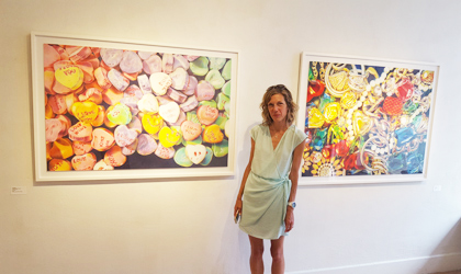 Kate O'Donnell stands in front of two of her pieces of art on display