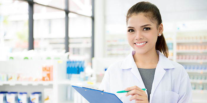 A woman stands in a pharmacy holding a clipboard