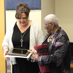 Cindy Hesse presents a plaque to Ms. Kathy during her retirement party on April 30.