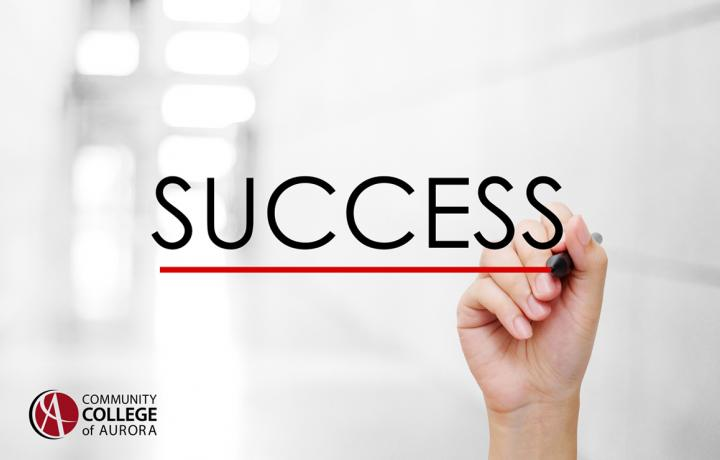A hand writing the word Success