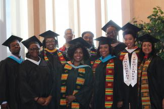 Black Faculty Staff Umoja members smiling in graduating caps and gowns