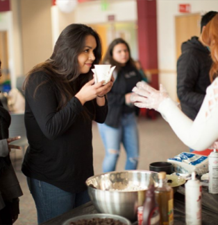 Photo of CCA student smelling a cup of hot chocolate at an event