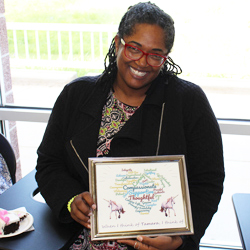 Tamara White shows off a plaque she received during her farewell party.